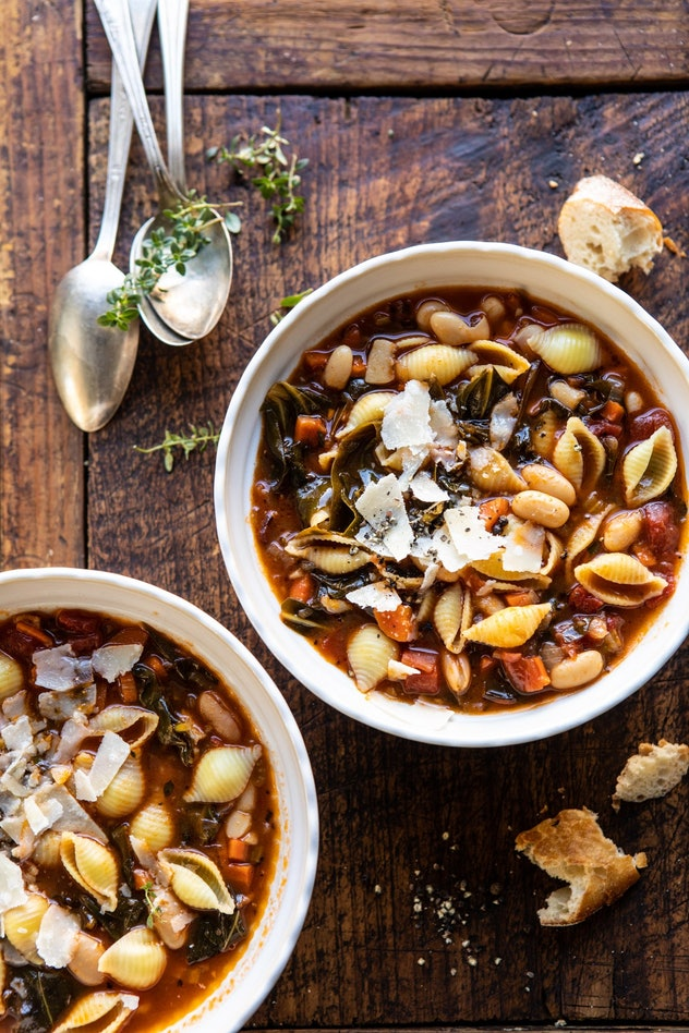 Pasta e fagioli sits in two white bowls on a wooden table.
