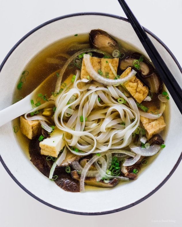 A white bowl of vegan pho sits on a white background.