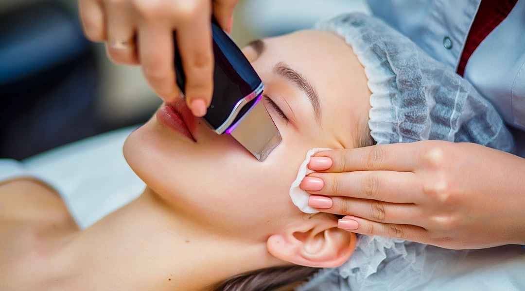 Woman receiving ultrasonic facial exfoliation at cosmetology salon. Procedure clearing clogged pores, ultrasonic treatment for skin rejuvenation, beautician uses modern apparatus for refreshing.