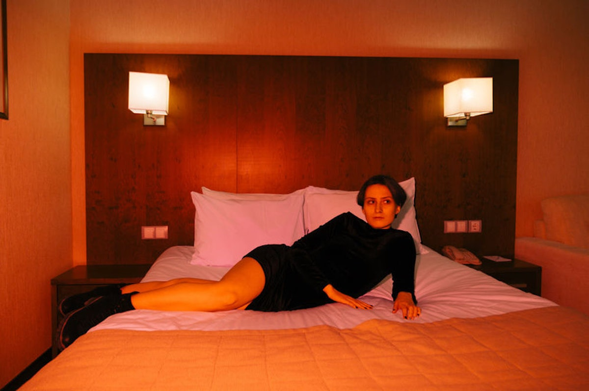 A woman lays on a hotel bed in black clothes and red lighting.