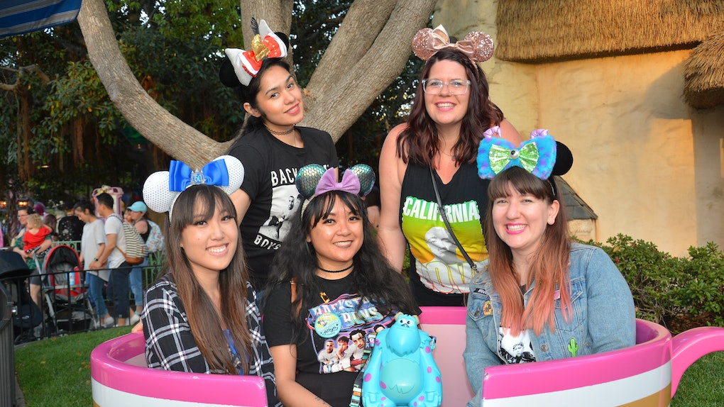 A group of friends wearing Minnie ears are sitting in a teacup spending a day at Disneyland.