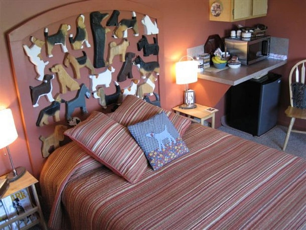 This cozy bedroom inside the Dog Bark Park Inn B&B has a dog-themed headboard and bed with three throw pillows.