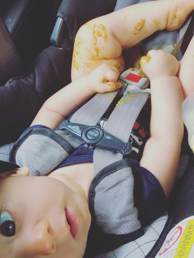 A 9-month-old baby sitting in his car seat, looking up at the camera and playing with his poop after a blowout.