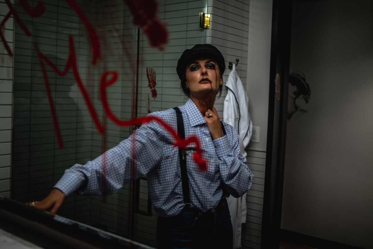 A woman with fake blood on her face and dark makeup stands in a mirror at Refinery's Hotel of Horrors.