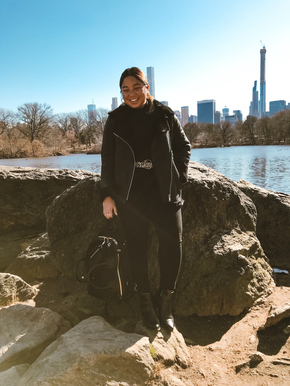 A woman in all black standing on a rock in New York City's Central Park with tall skyscrapers in the background is smiling.