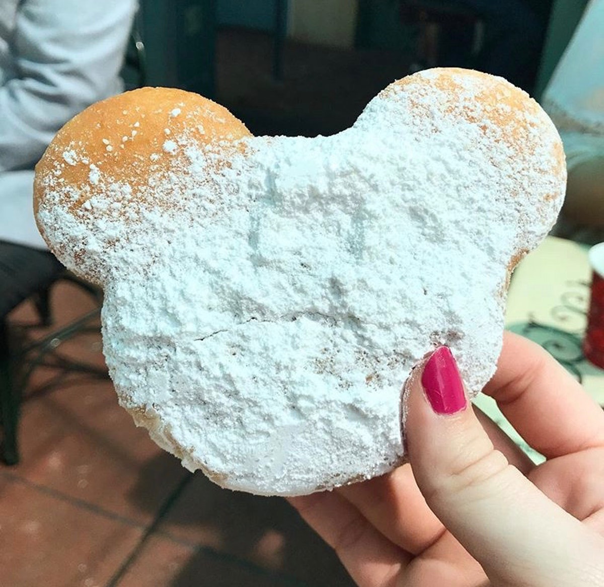 A Mickey Mouse-shaped beignet at Disneyland needs a Mickey-shaped food caption for Instagram.