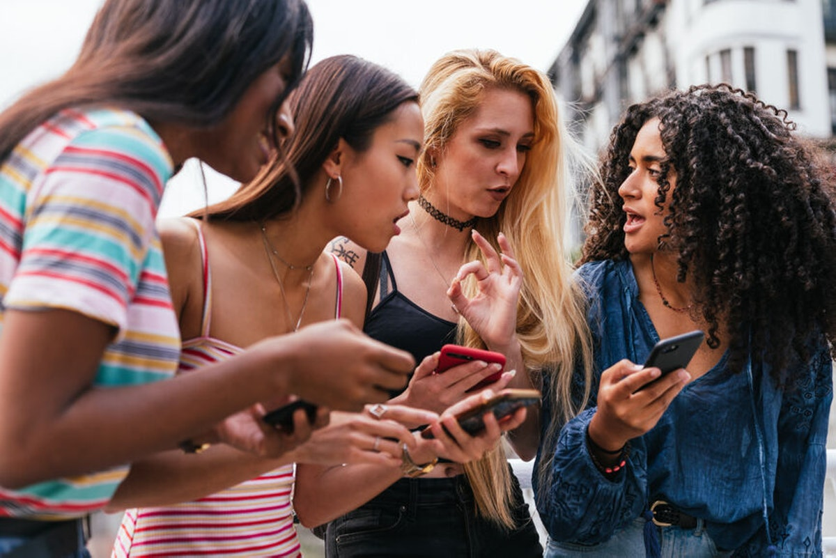 A group of diverse friends look at their phones.