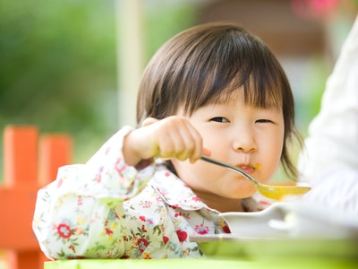 A little girl eating soup