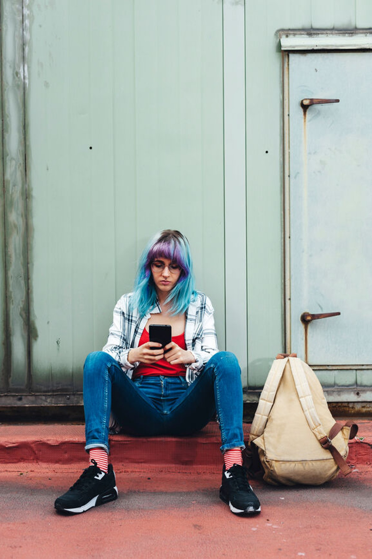 A girl with blue and purple hair sits on a red sidewalk in street clothes and types on her phone.