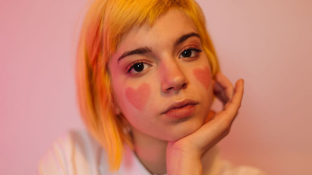 A teenage girl with short dyed hair and hearts painted on her cheeks looks like an e-girl.