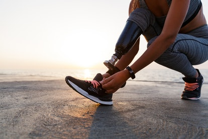 A vegan athlete laces up sneakers on their prosthetic leg.