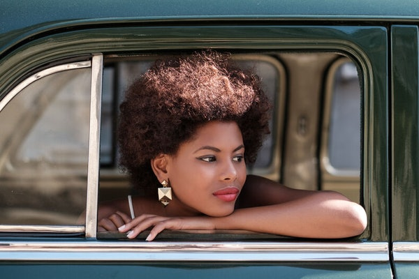Woman smiles wearing earrings and looks out of the window of a vintage car.