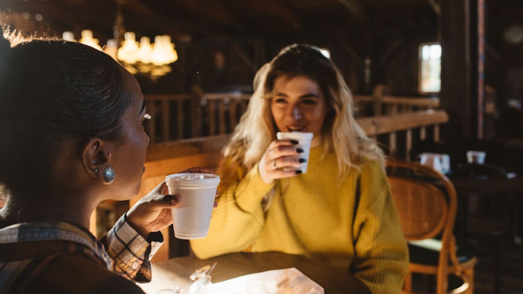 Two friends drink apple cider and chat at a cider mill in the fall.