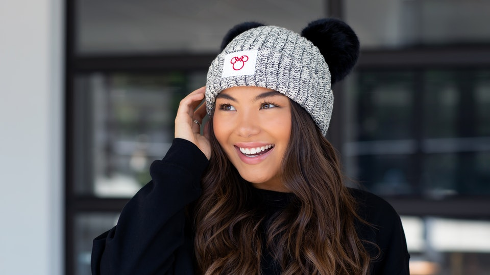 Young woman wearing a hat from the Disney and Love Your Melon Collaboration