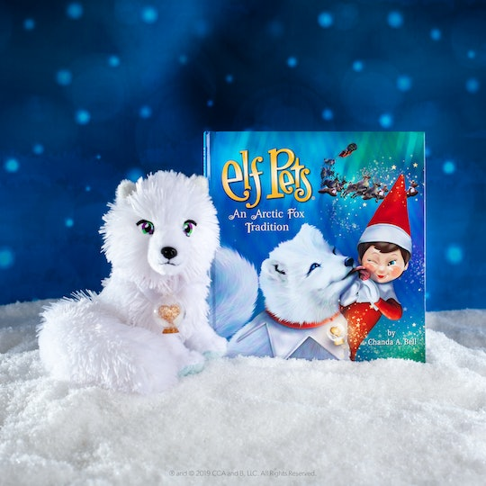 lifestyle shot of Elf Pets: An Arctic Fox Tradition book and arctic fox plus in fake snow
