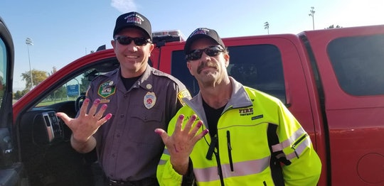 Two firemen model their freshly painted nails after rescuing a little girl from a car accident.