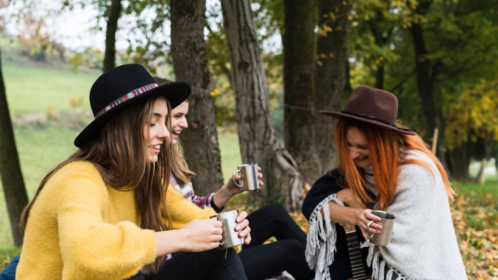 A group of friends laugh and drink tea during a fall picnic.