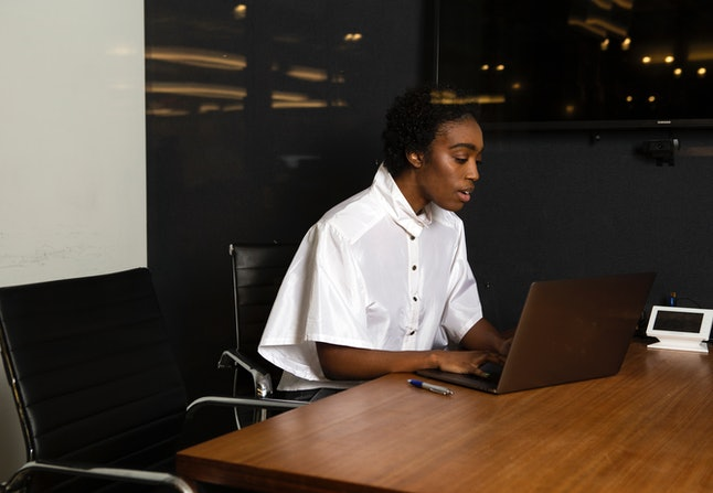 A non-binary person using a laptop at work. Employees who are multiply marginalized are more likely to be expected to work outside of office hours.