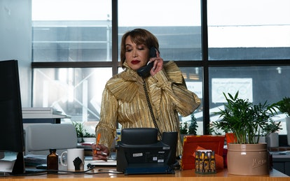 A transfeminine executive using the phone in her office with an orange pen. Staying connected to your workplace after hours may help some people, but for marginalized employees, these expectations can be damaging.