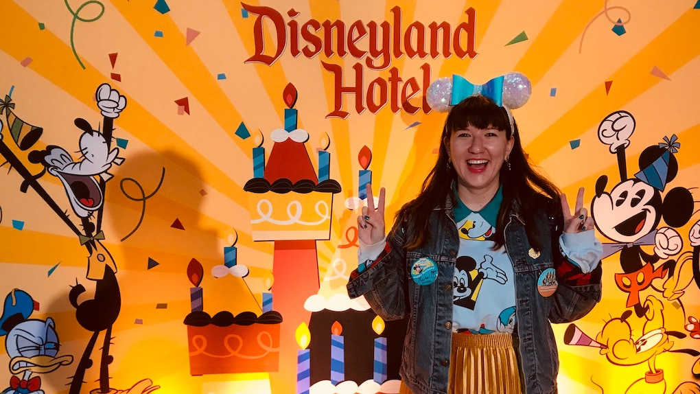 A woman wearing sequinned Minnie ears stands in front of a birthday Disneyland Hotel sign at Disney.