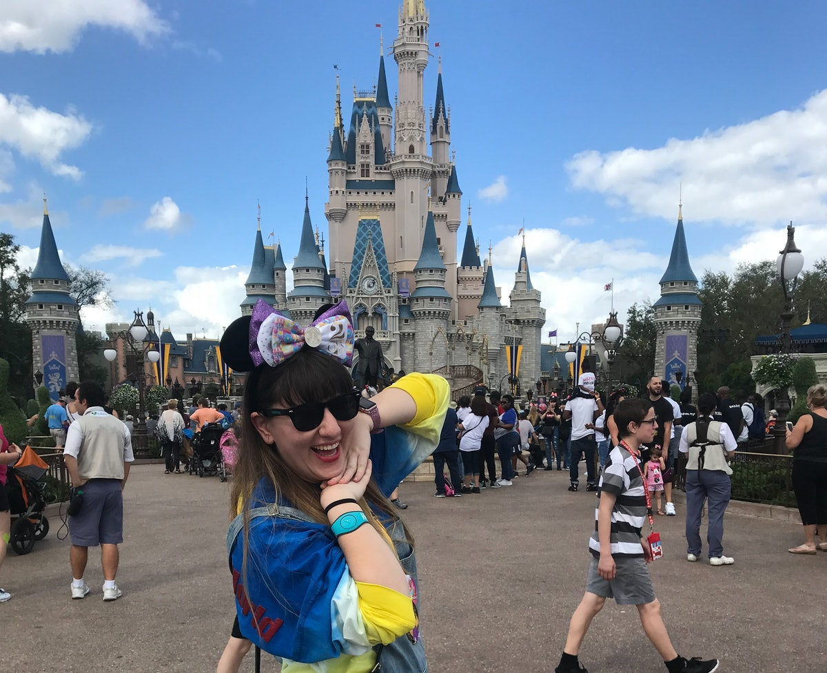 A woman posing in front of Cinderella's castle at Disney World.