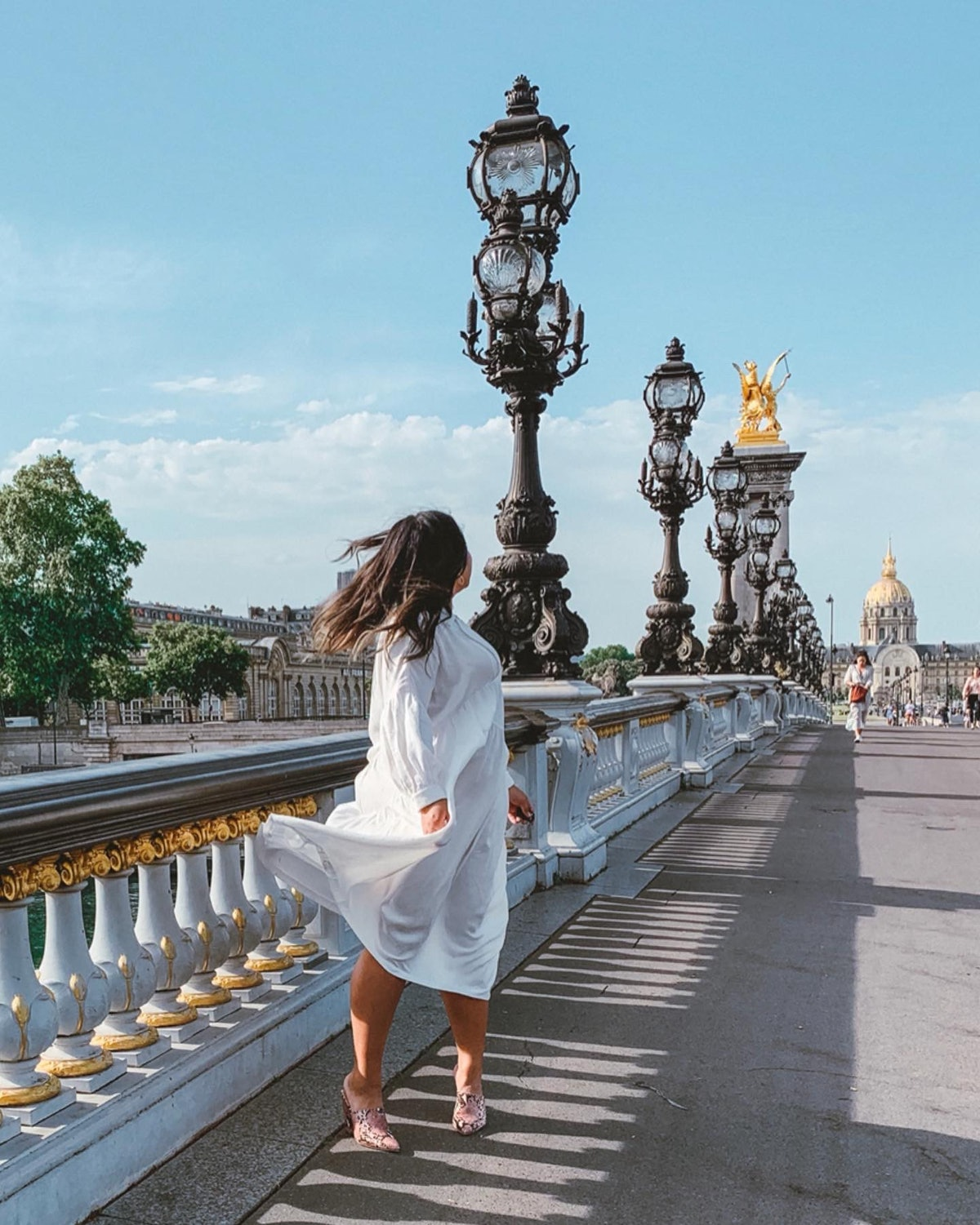 A woman in a flowy white dress poses with her hair blowing in the wind on the Pont Alexandre III.