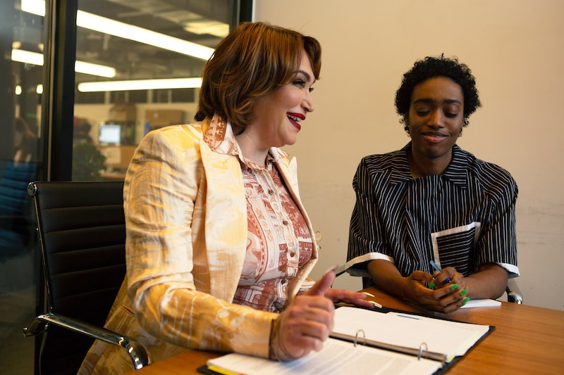 Two colleagues, a transgender woman and a non-binary person, laughing in a meeting at work. Fear of missing out at work might hurt your mental health, a new study says, but that might not be the full story.