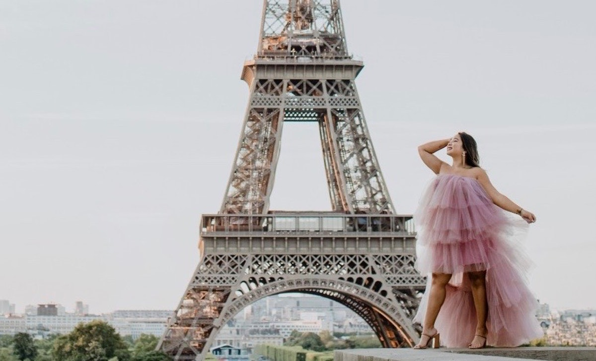 A girl dressed in a pink tulle dress smiles and poses in front of the Eiffel Tower in Paris.
