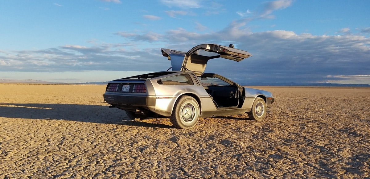 The Delorean DMC-12 car from 'Back to the Future' has vertical-opening doors and is parked in the sunshine.