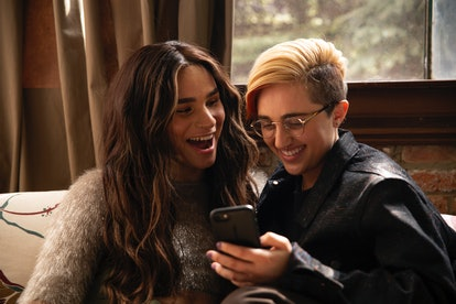 A transfeminine non-binary person and transmasculine gender-nonconforming person looking at a phone and laughing. If your texting style is similar to your friends or romantic partners', you're less likely to feel texting anxiety, science says.