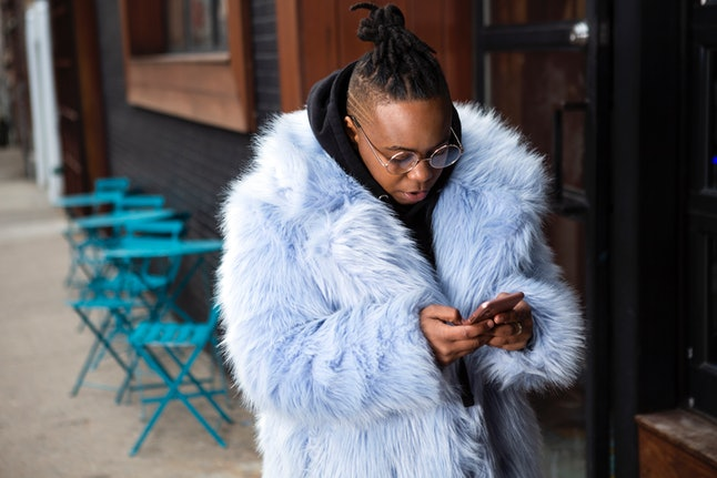 A transmasculine person with a furry blue coat checking his phone on the sidewalk. Your brain likes the unpredictability of receiving texts, but the uncertainty is also anxiety-provoking.