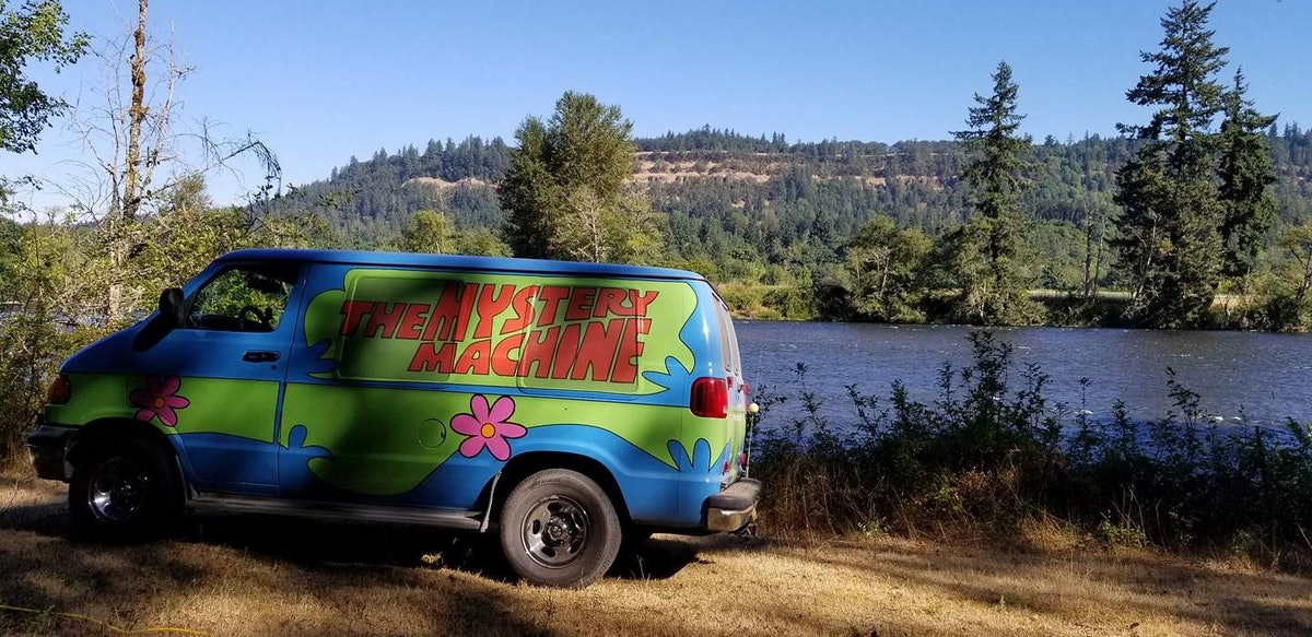 The Mystery Machine from 'Scooby Doo' sits near a lake, surrounded by a bunch of trees.