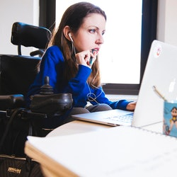 A woman sit in her wheelchair working at her desk with a pen in her mouth, while staring at a computer screen. According to the ADA National Network, disabled people are allowed to ask for reasonable accommodations in the workplace.