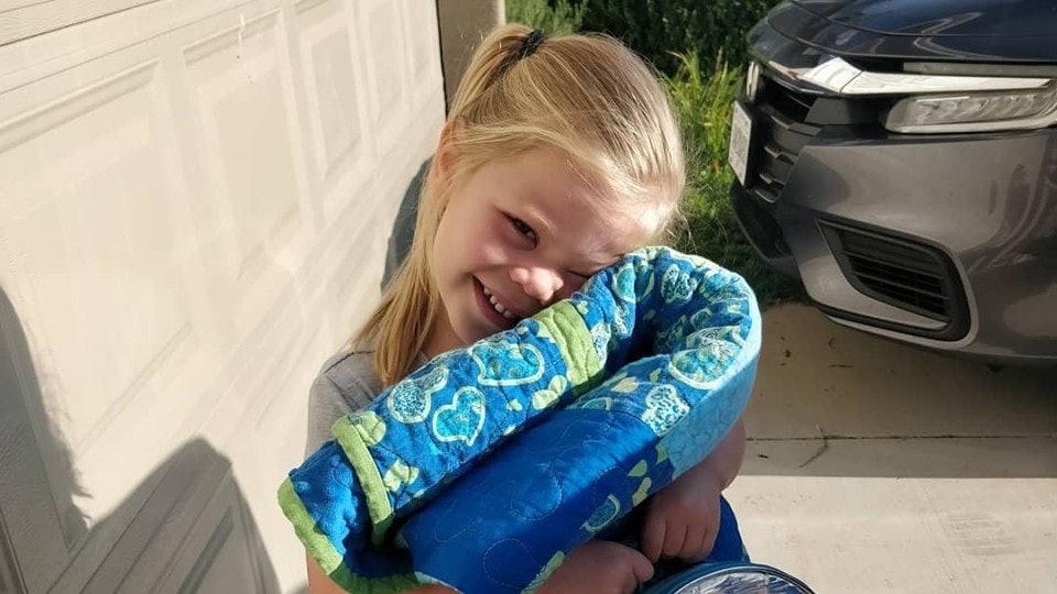 Girl cuddles her backpack