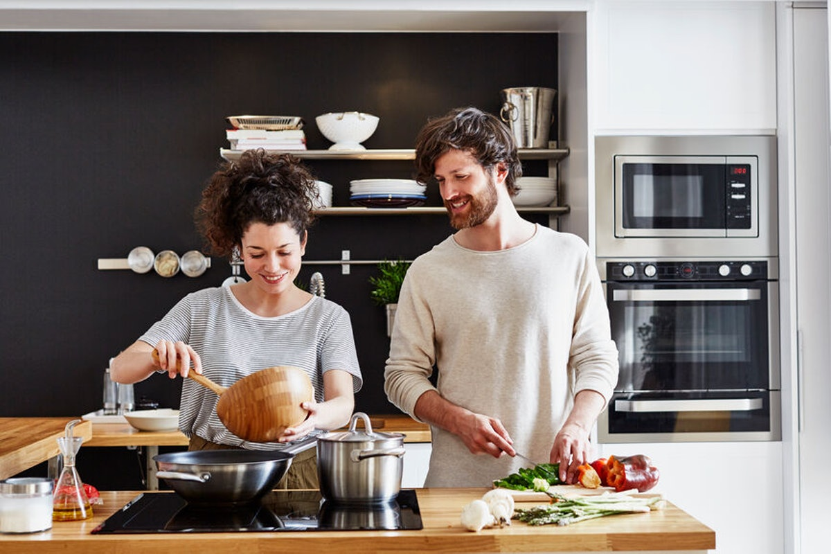 A happy couple cooks in their kitchen together.