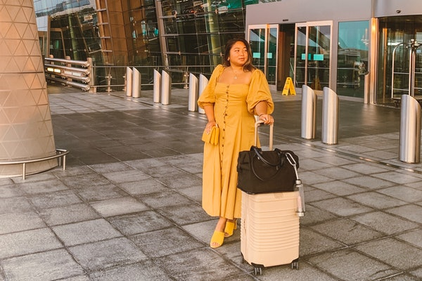 A woman in a long button-down yellow dress and yellow shoes stands in front of an airport with her beige suitcase, proving all the benefits of a carry-on.