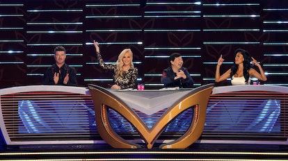 The Masked Singer judges sit at their desk