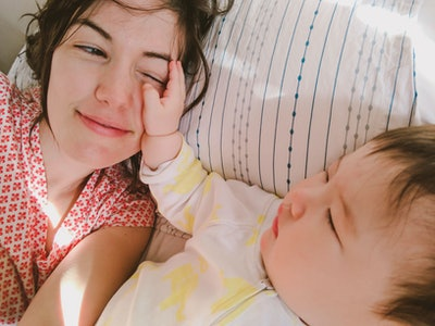 a mom lies in bed with her baby