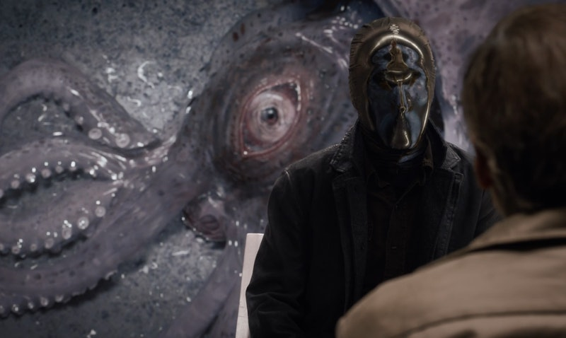 """An image of a squid behind Tim Blake Nelson as """"Looking Glass"""" in Watchmen"""