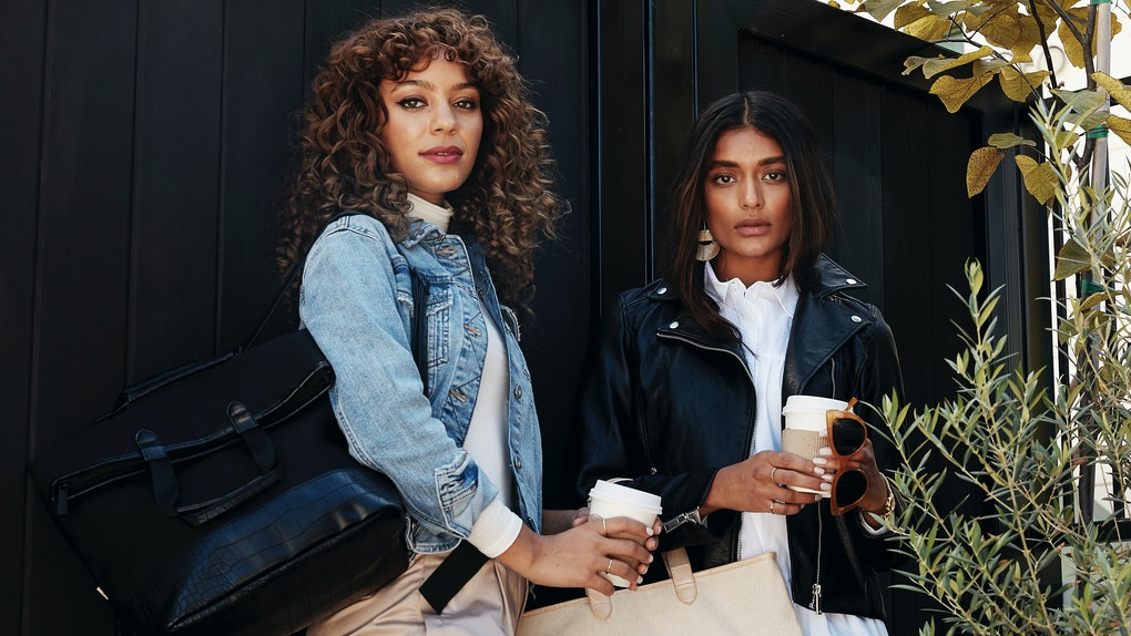 Two girls stand in front of a black fence with coffee cups and bags from Shay Mitchell's BÉIS winter collection.