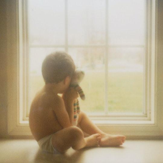 Boy holds teddybear in window