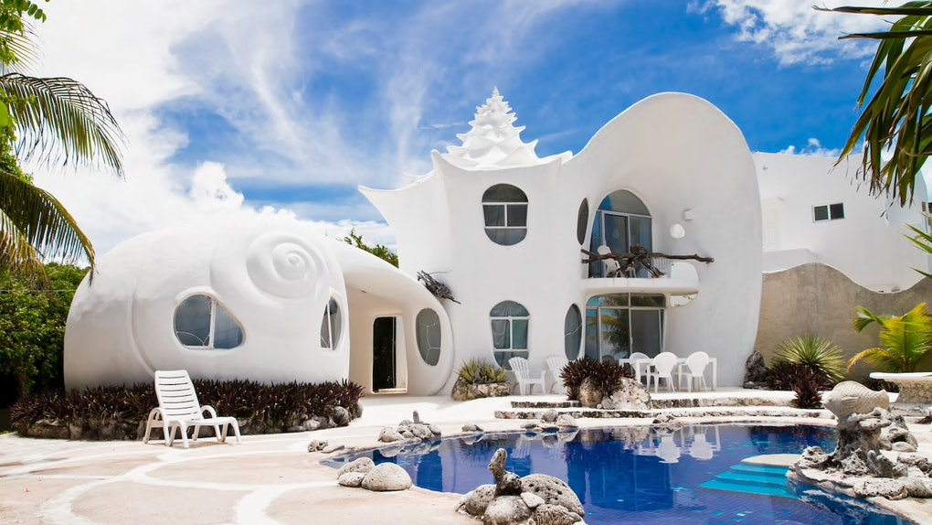 The exterior of the Seashell House on Airbnb features a private pool and unique white architecture.