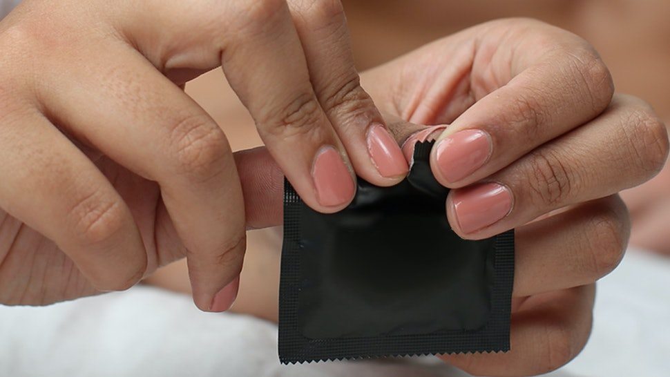 A person with pink nails rips open a condom wrapper. Condoms are still one of the only male birth control options.