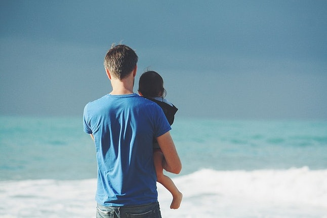 A parent looks over the ocean with their child. The U.S. is the only industrialized country worldwide without federal laws mandating parental leave.