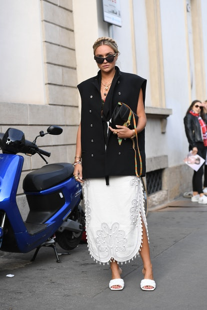 Street style photo of a woman wearing a boxy, oversized vest and white lace dress with Bottega Veneta sandals at Fashion Week.