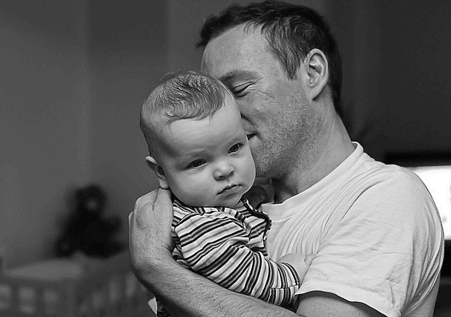 A father holds their baby. Equitable parental leave may help the motherhood wage penalty over time, experts say.