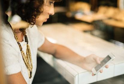 A person scans emails on their phone. Long-term stress responses to after-hours work can have negati...