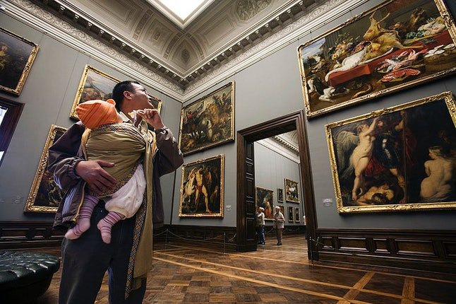 A father takes a child to a museum. Daddy quotas, or periods of non-transferable paternity leave, help decrease the income wage gap between partners, say studies.