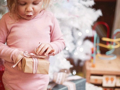 A young child opens up holiday gifts.