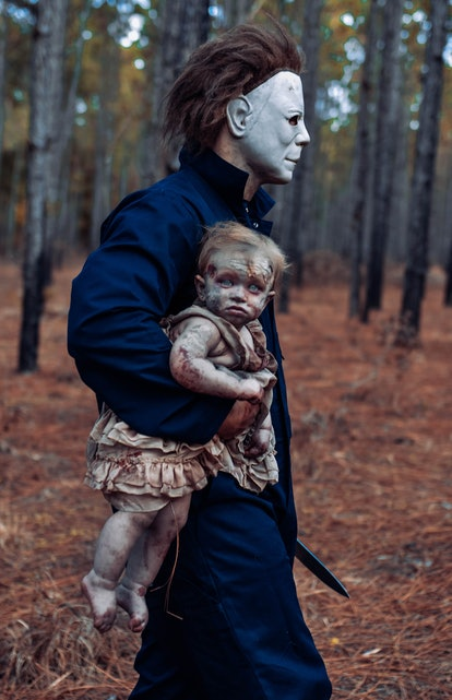 A dad dressed as Michael Myers carries his zombie baby away.